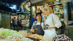 Barcelona, Spain - A woman buys sweets at the famous Boqueria Stock Footage