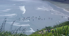 Swimmers at Murawai Beach coastline in Auckland, New Zealand Stock Footage