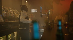 4K Bar staff & customers dancing & enjoying the atmosphere in lively nightclub Stock Footage