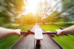 Riding a bike first person perspective. Smartphone attached to handlebar. Spe Stock Photos