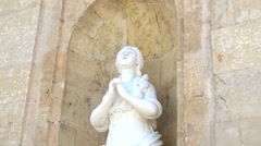 Zoom out statue of saint at the entrance to Cathedral Stock Footage