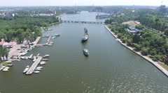 Aerial video. Warships maneuver in the river harbor at the shipyard Stock Footage