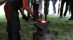 Blacksmith working on metal on anvil at forge - stock footage
