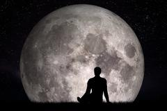 Man sitting alone on grass and looking on moon. Imagine the future concept. Stock Photos