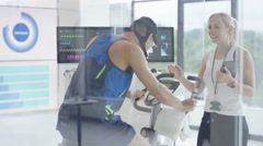 4K Man on exercise bike having fitness levels analyzed with hi tech equipment Stock Footage