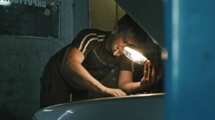 Car mechanic with a cigarette in his mouth fixing a car in the garage, wide - stock footage