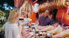 Barcelona, Spain - Woman slicing jamon orders. Seller Stock Footage