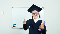 Cute graduate in the mantle holding a book. Portrait little student girl 7-8 Stock Footage