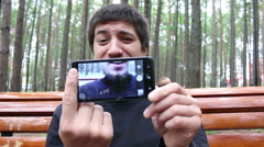 Man shoots funny selfi video on phone in forest Stock Footage