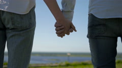 Loving Couple Walking On The Grass In Park. Loving Couple Holding Hands - stock footage