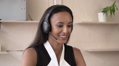 Young professional woman talking on the headset with friendly smile Stock Footage