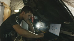 Car service, computer diagnostics: mechanic repairs the damage using the pc Stock Footage