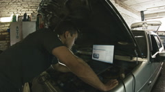 Car service, computer diagnostics: mechanic repairs the damage using the pc in Stock Footage