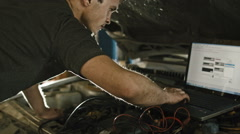Computer diagnostics in car service: mechanic repairs the damage using the pc Stock Footage