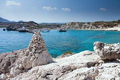 Kolymbia beach with the rocky coast in Greece. Cruise ship coming in the port Stock Photos