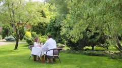 Couple in the white bathrobes have breakfast in the garden Stock Footage