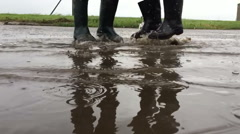 Jumping together on a puddle slow motion Stock Footage
