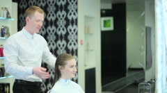 Man hairdresser combing girl's hair - stock footage