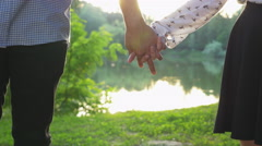 Close-up of couple holding hands at sunset and walking together Stock Footage
