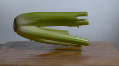 A celery stalk bounces in slow motion onto a cutting board - stock footage