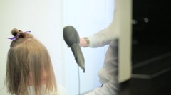 Hairdresser dries the girl's hair with dryer Stock Footage