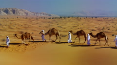 Camel caravan train travelling across a Middle Eastern desert - stock footage