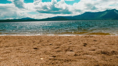 Waves crashing gently on quiet sandy beach. mountain background. 4K footage Stock Footage