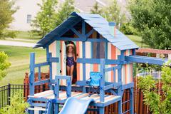 Single little girl peeking from doorway on playset - stock photo