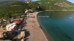 Top view at the sandy beach Jaz with sunbathing and swimming people. Budva Stock Footage