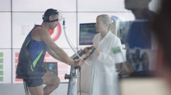 4K Sport scientist in white coat assessing fitness of man on exercise bike Stock Footage