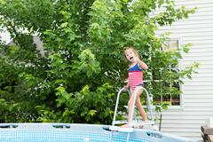 Happy five year old girl entering swimming pool - stock photo