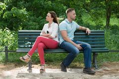 Unhappy Couple Sitting Back To Back On Bench In Park - stock photo