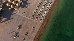 Sunbeds and parasols on pebble. Adriatic sea. Budva municipality, Montenegro Stock Footage