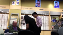 Man filling a form to buy eyeglasses at Image Optometry store Stock Footage