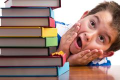 Shocked young boy looking at his textbooks - stock photo