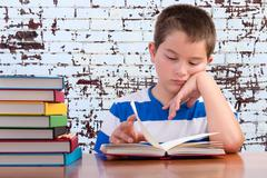 Elementary schoolboy focusing on his studies - stock photo