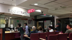 People sitting in a hospital emergency registration area. Stock Footage