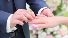 Groom wears ring on the bride's finger Stock Footage