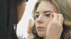 Makeup artist sticks the eyelashes to the girl - stock footage