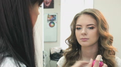 Hairdresser combing the hair of a beautiful model - stock footage