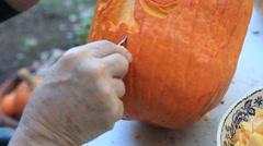 Closeup man carves Halloween pumpkin Stock Footage