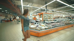 Girl chooses the item on the shelves in the store Stock Footage
