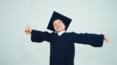 Happy graduate girl 7-8 years in the mantle and hat holding diploma on white - stock footage