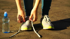 Girl stopped running to tie the laces on running shoes. fitness girl training Stock Footage