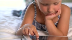 Little cute girl plays a game on the tablet Stock Footage