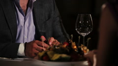Man in jacket, purple shirt sitting at table in restaurant with woman. Romantic Stock Footage