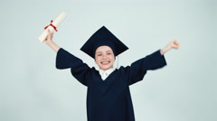 Happy student graduate girl 7-8 years child has diploma and dancing with - stock footage