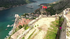 National Montenegrin flag waves on wall of castle St. John, Kotor, Montenegro Stock Footage