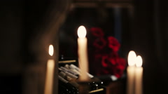 White candles burning. Fire. Bouquet of red roses on background. Flame - stock footage