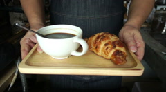 Ready for a cup of coffee and fresh croissant on wooden tray, slow motion - stock footage